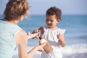 Image of Mom putting sunscreen on child