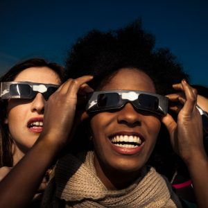 Image of people looking at eclipse through safety glasses.