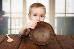 image of hungry child with empty bowl