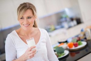 Image of young woman drinking glass of milk
